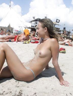 Slim girl with perky boobs naked at a nudist beach